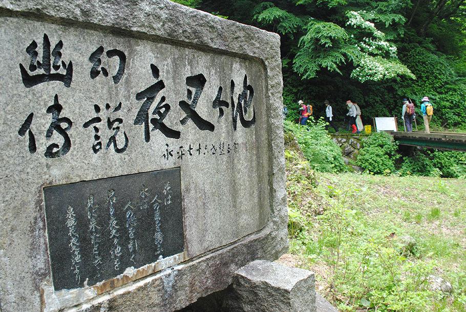 文学碑に見送られて歩く始めた登山者たち