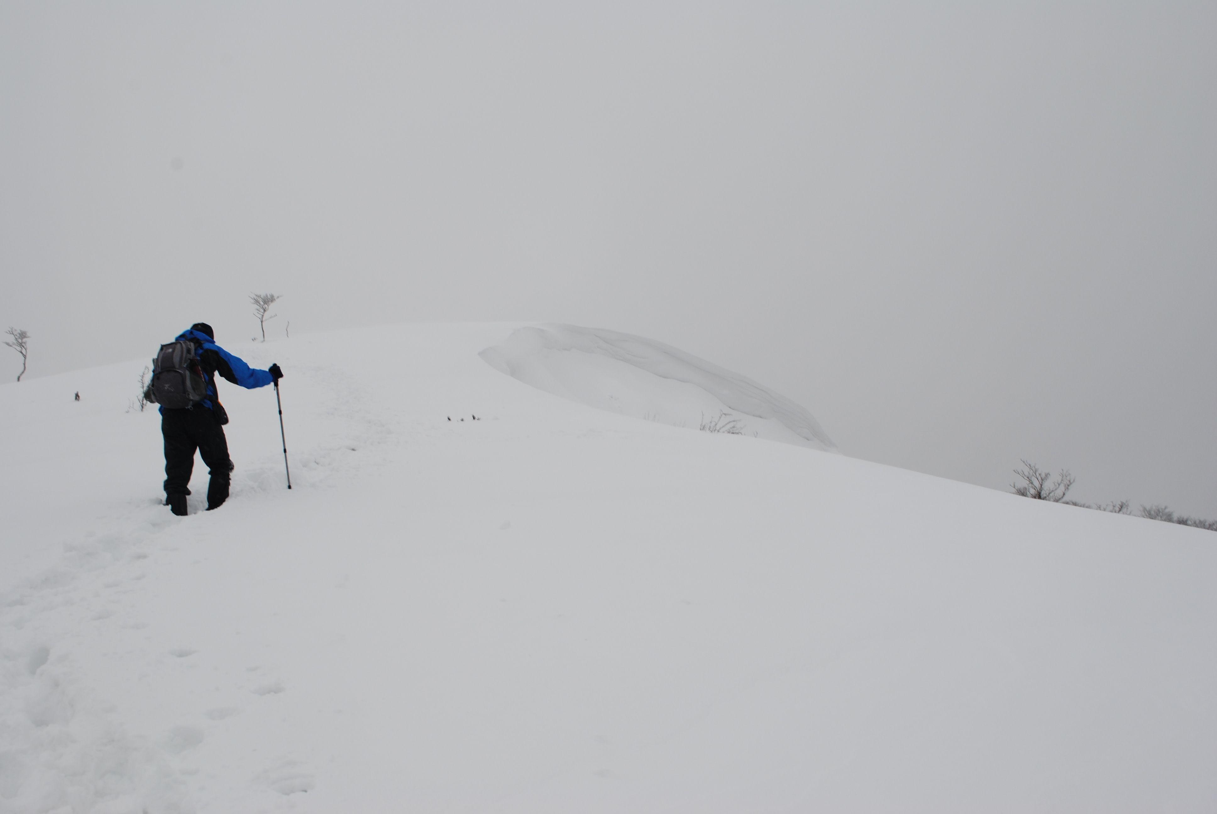 分厚い雪の稜線を慎重に歩く
