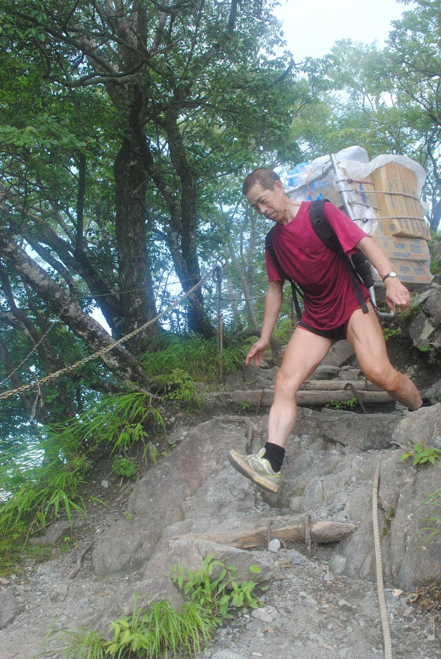 岩場を下る。ひざに荷物の重さがかかる。微笑みから真剣な表情になる