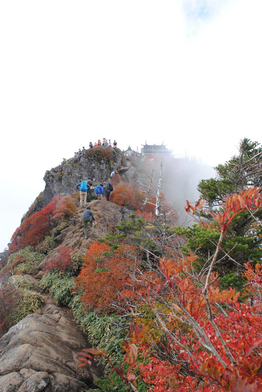 天狗岳の稜線から弥山を望む。山頂には大勢の登山者がいる