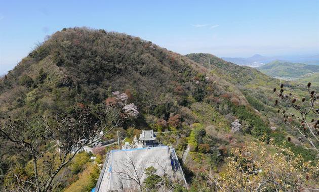 7歳の弘法大師が身を投じた捨身ケ岳禅定からの景色。下に見える屋根は出釈迦寺奥の院、向かいの中山、その左の火上山(ひあげやま)の向こうに瀬戸内海が広がる。弘法大師も西行法師も目にした景色だ=善通寺市吉原町で
