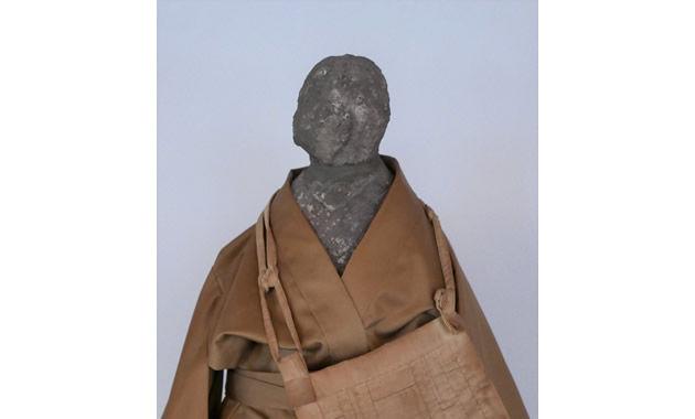 玉泉院境内の西行庵に祀られている石造りの西行像。僧衣の下は風呂敷包みを背負い胸の前で結ぶ「西行背負い(じょい)」になっている。顔は壊されたのだろうか=善通寺市南町3丁目で