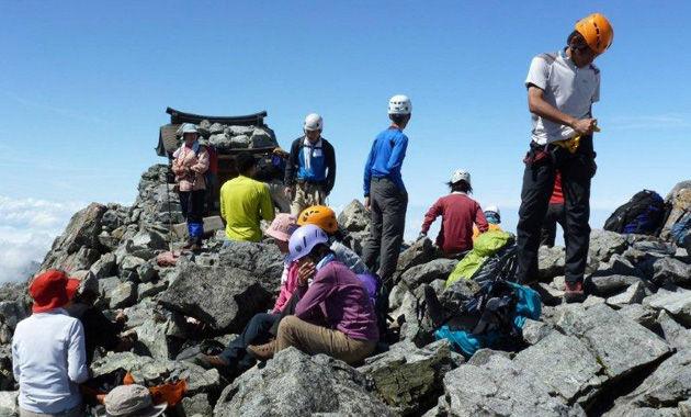 剱岳山頂はヘルメットをかぶった登山者が多い(イメージ)
